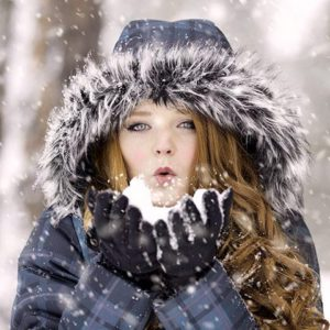 woman-blows-snow-from-gloves_large
